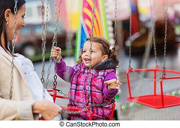 Mother and daughter at fun fair, chain swing ride - Cute...