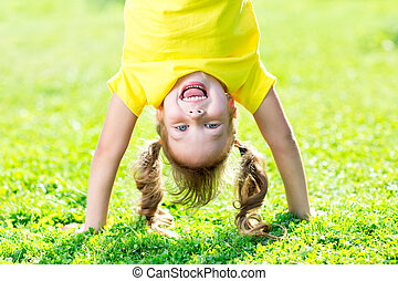 Portraits of happy kid playing upside down outdoors in summertime standing on hands on grass