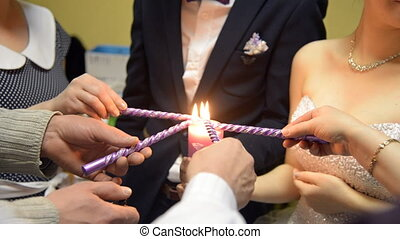 Parents of bride and groom lighting candle