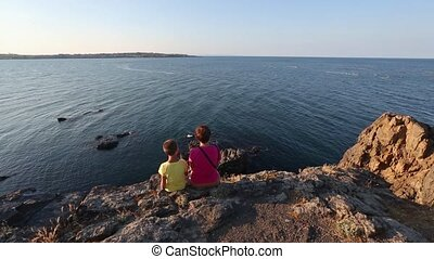Family on Rocky Sea Coast. - Mother with son on summer sea...