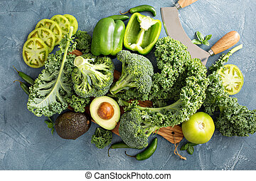 Variety of green vegetables on the table including kale,...