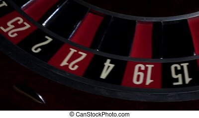 Usual roulette wheel running with white ball, top view -...