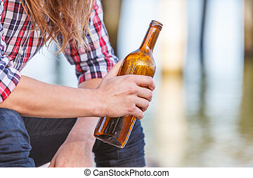 Man depressed with wine bottle sitting on beach outdoor...