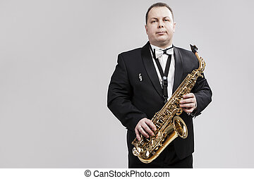 Man with Saxophone in Suite Posing Against White Background...