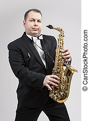 Relaxing Caucasian Man Posing With Saxophone Against White...