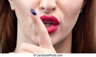 Woman holding her finger to her lips in a gesture for...