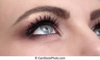 Woman with beautiful blue eyes and long black eyelashes and...