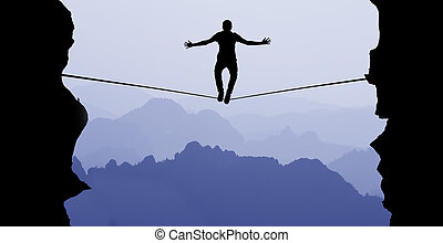 Man balancing on the rope challenge and risk taking concept...