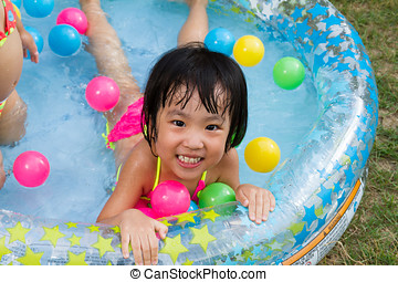 Asian Little Chinese Girl Playing in an Inflatable Rubber...