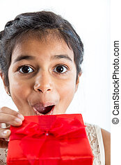 Excited girl gets gift - Close-up of a young girl opening a...