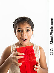 excited girl opening gift - A young girl of Indian ethnicity...