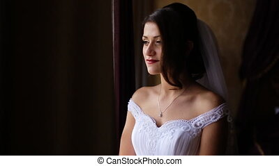 Young beautiful bride stand near the window and her handsome groom touch her shoulder. A very romantic atmosphere on the room.