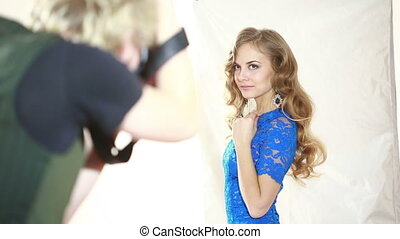 Back view of a man with camera taking a photo fashion model