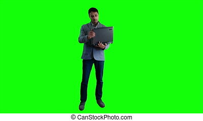 Man working with laptop on the background of a green screen