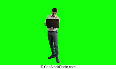 A man working on a laptop on a background of a green screen