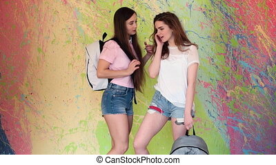 sexy young girls in denim shorts, talking to each other on...