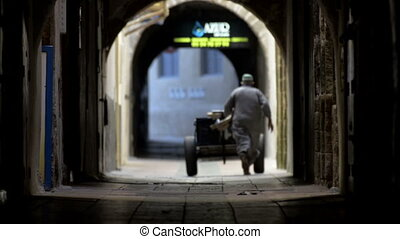 Seller with cart in old tunnel of ancient city Essaouira, Morocco
