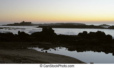 View on ocean and beautiful silhouette of rocks at sunset in...