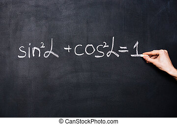 Hand writing trigonometry formula on blackboard with chalk