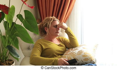 Blonde woman under pressure sitting on a sofa in living room