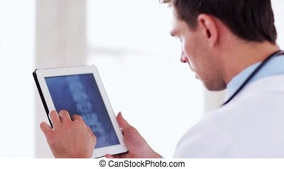 doctor working with x-ray scan on tablet pc - professional...