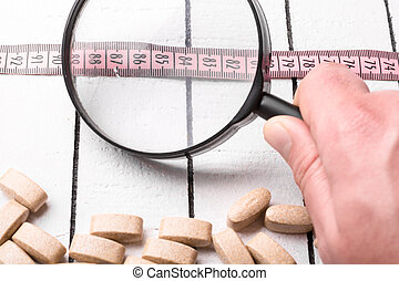 Pills, pink measuring tape and hand holding a magnifying...