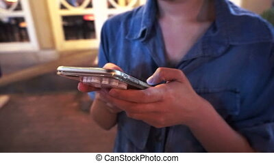 woman using her smart phone - close up of woman using her...