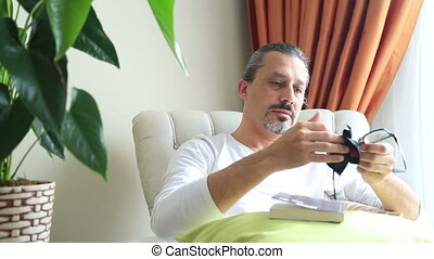 Man cleaning eye glasses - Man sitting on couch at living...
