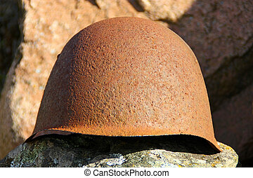 Helmet - Old rusty helmet on the rock