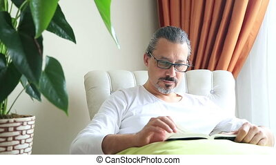 Middle aged man reading a novel - Middle aged, brunette man...