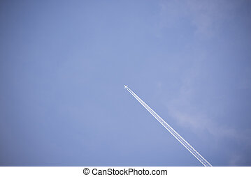 jet and its vapour trails in a cloudy blue sky