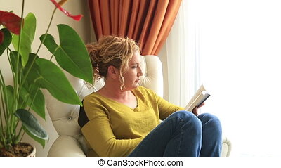 Blonde woman reading book on couch