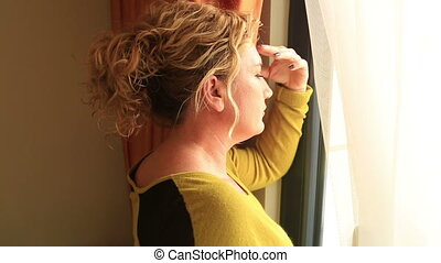 Sad woman looking out the window - Sad woman standing next...