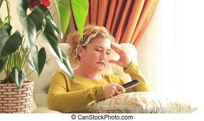 Sleepiness, yawning woman watching television