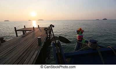 Thai fishing boat and wooden catwalk on the sea coast during...