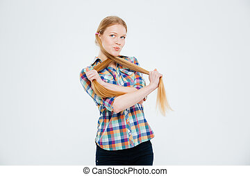 Funny woman holding her ponytails isolated on a white...