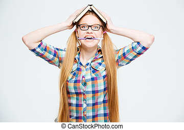 Funny female student with book on head biting pen
