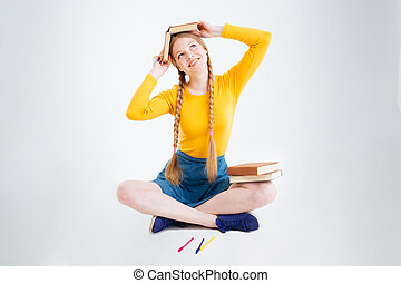 Happy female student sitting on the floor with book
