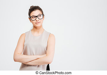 Beautiful thoughtful young business woman standing with arms...