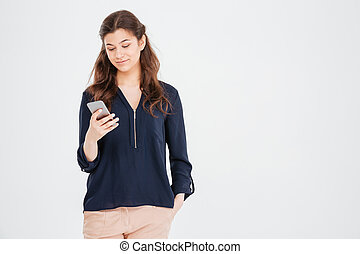 Attractive smiling young woman standing and using smartphone...