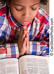 Mulatto boy praying.
