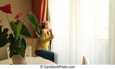 Thoughtful woman looking out her window waiting for something