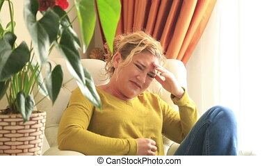 Sick, painful woman sitting on sofa - Woman having a painful...
