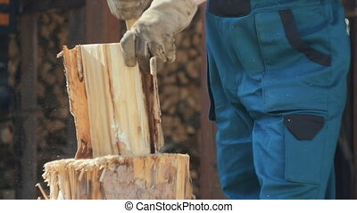 Man Preparing House for Winter - House owner splitting logs...
