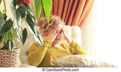 Woman having headache migraine - Woman sitting on a couch...
