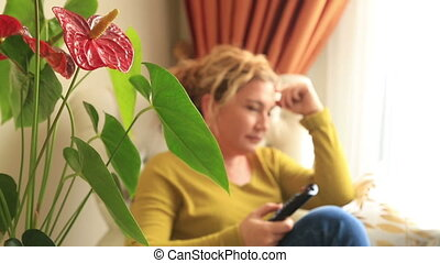 Woman on couch watching tv - Smiling middle aged woman...