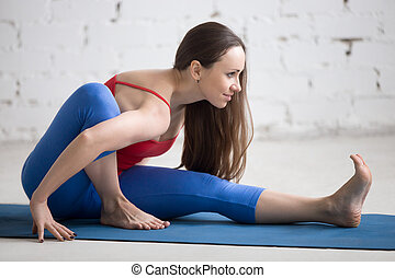 Yoga Indoors: Marichyasana I pose - Portrait of beautiful...