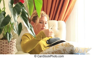 Woman putting on glasses, reading - Woman putting on glasses...