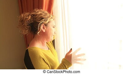 Woman looking out the window - Woman standing next to and...