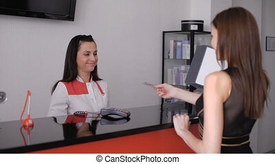 young beautiful brunette, paying by credit card. Cosmetology Clinic.
